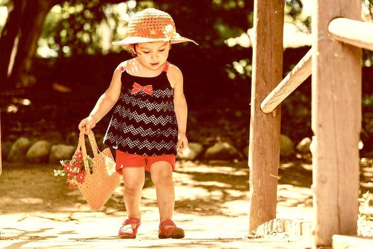 Kislány virágos fonott kapallap és virággal teli fonott szatyorral sétál