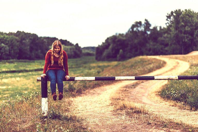 Lány ül a földút feletti sorompó rúdján
