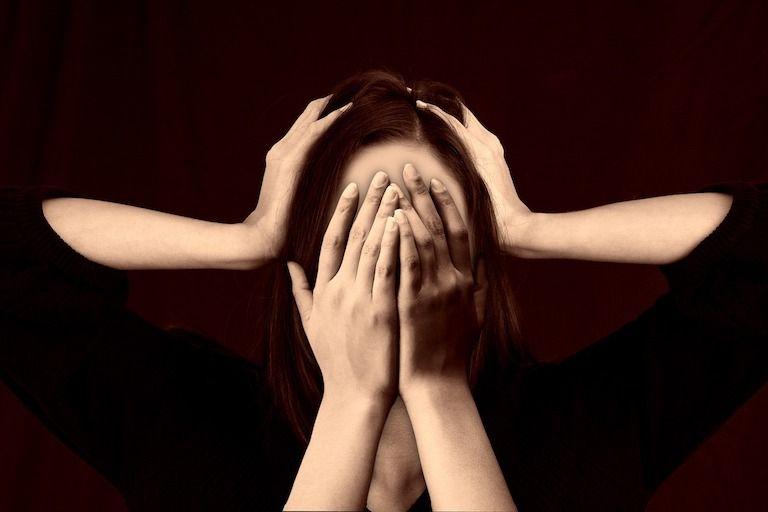 Nő fekete felsőben két kezzel fogja a fejét és az arcát