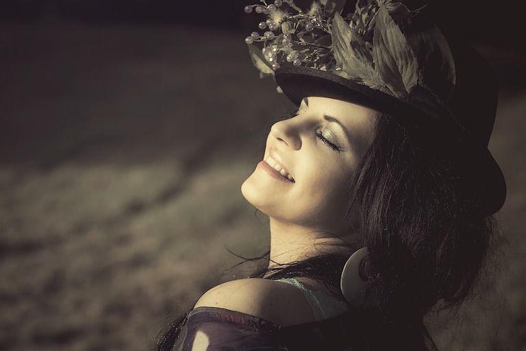 Nő furcsa tollas kalapban büszkén vállalva személyiségét