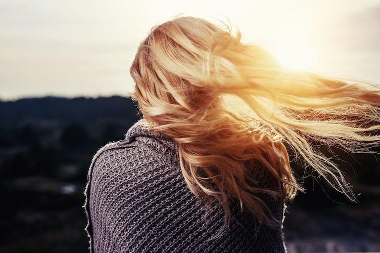 Szőke nő hátulról naplementében, szőke haját jobbra fújja a szél