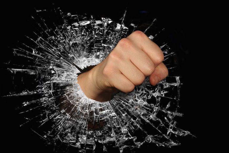 Egy ököl, amint átüt egy üvegfalat