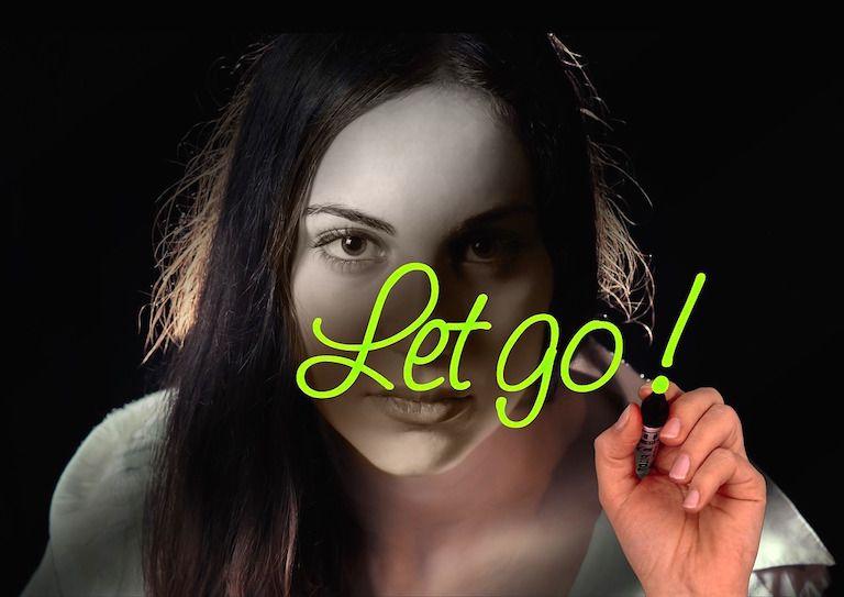 Nő zöld filccel üvegre írja, hogy Let go!