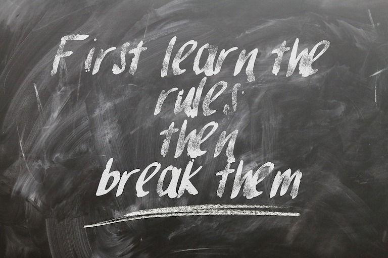 Fekete táblán kréta felirat: Először tanuld meg a szabályokat, utána szegd meg őket