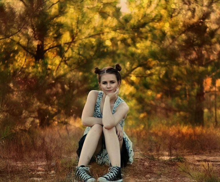 Kamasz lány ül az avarban, állát a kezere támasztja