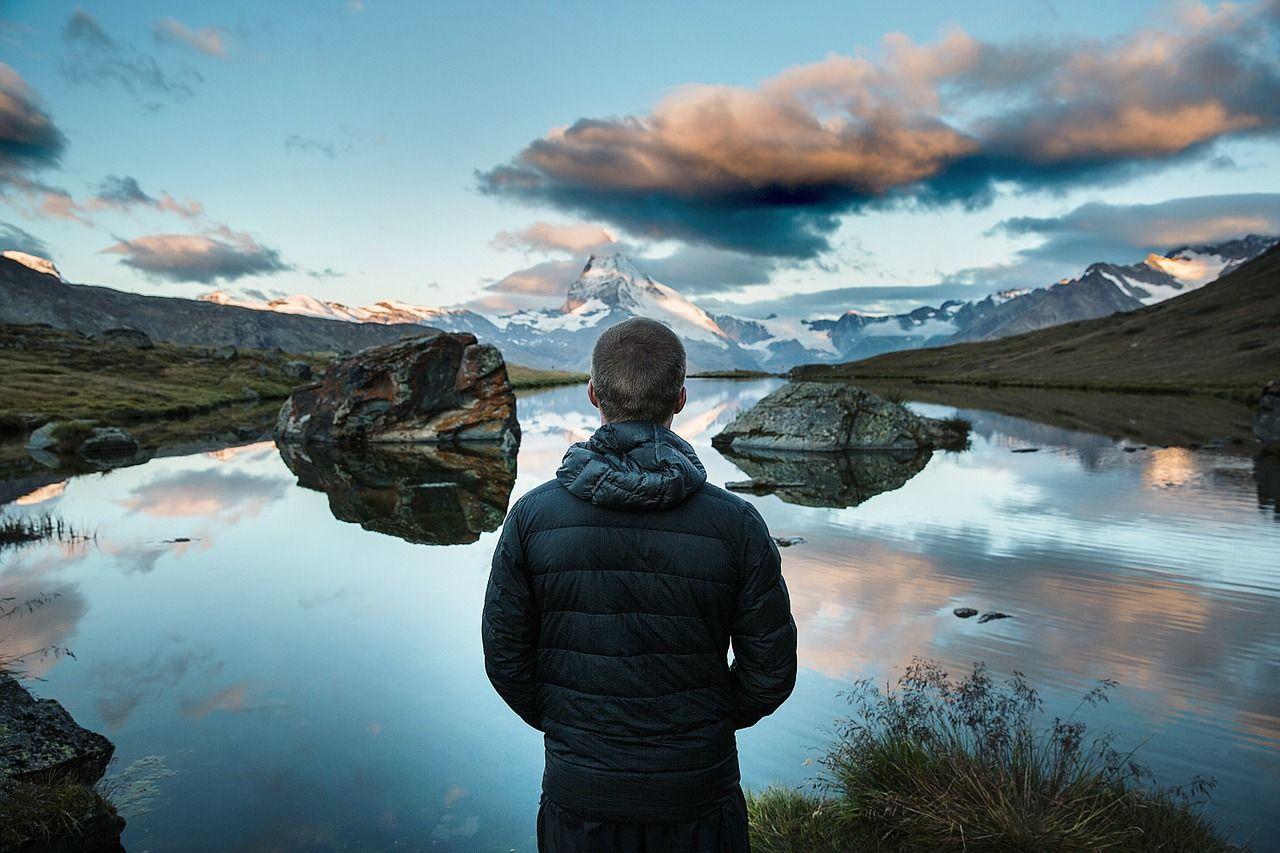 Egy férfi háttal néi a tavat és a tájat maga előtt.