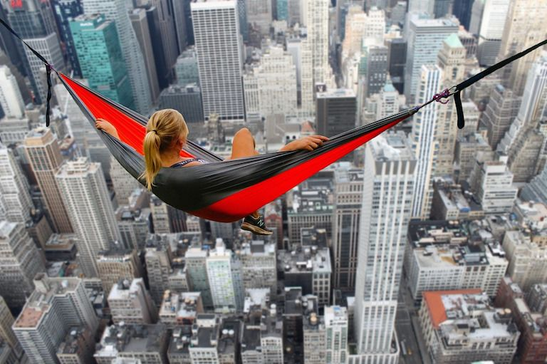 Egy nő függőágyon a felhőkarcolók felett