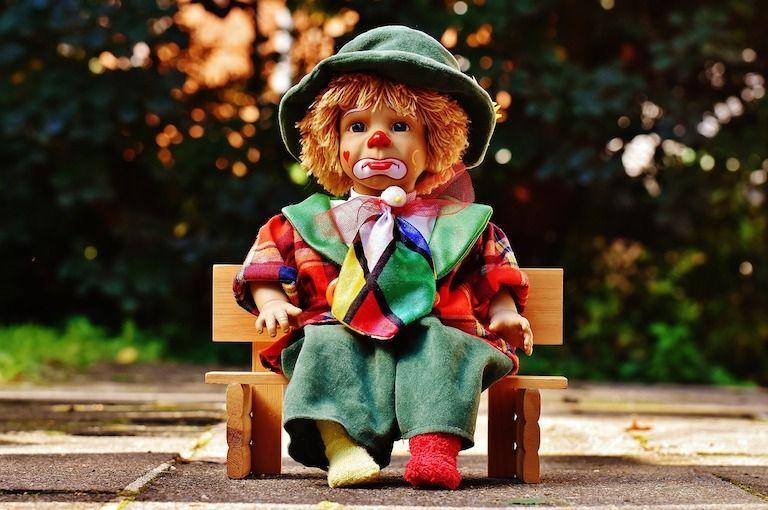 Bohócknak öltöztetett játékbaba kis padon lefelé biggyedő ajkakkal