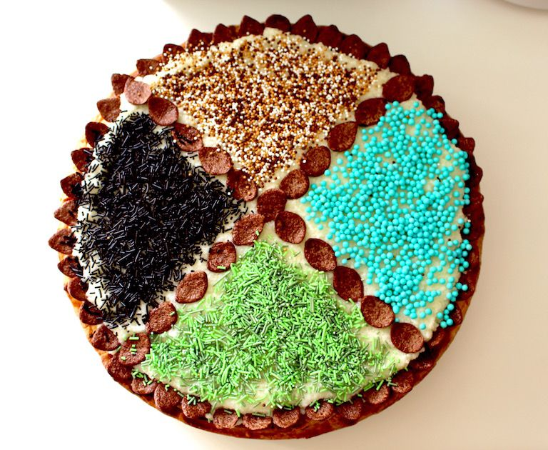 Négy negyedre osztott születésnapi torta zöld, világoskék, fekete és barna szórt díszekkel felülről