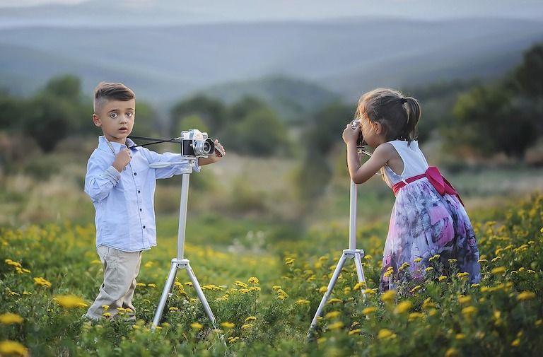Egy kisfiú és egy kislány egymással szemben állnak a mezőn miközben fotózzák egymást