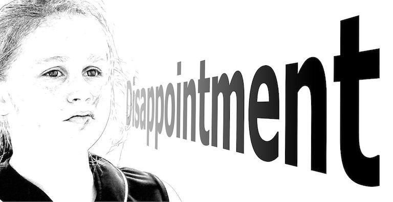 Fekete-fehér kép, szomorú arcú kislány előtt a disappointment (csalódás) szó