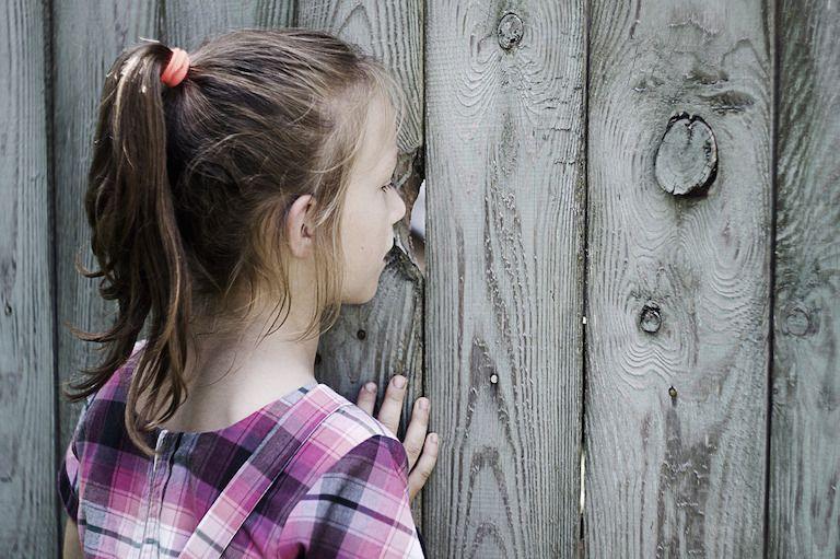 Egy kislány átnéz egy kerítés lyukán
