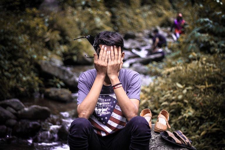 Ülő férfi az arcát a tenyereibe temeti egy sziklás patak partján