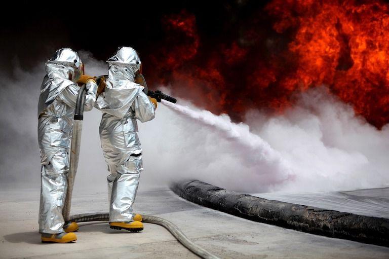 Két tűzoltó ezüst védőruhában tűzet olt