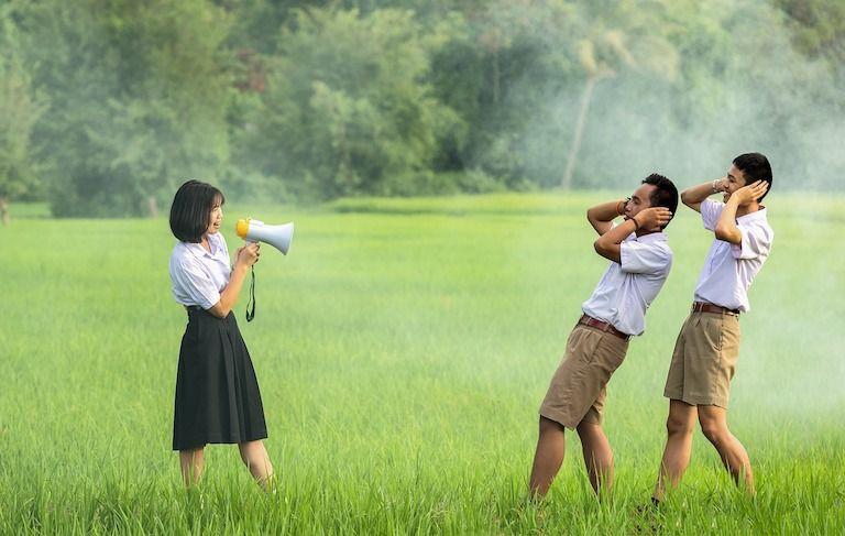 Ázsiai nő mezőn hangosbeszélőbe beszél miközben két férfi a fülét befogva hátrahőköl