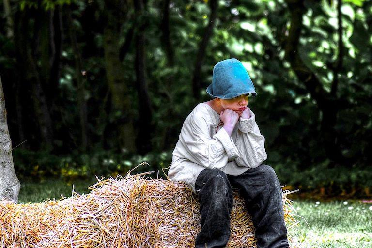 Kisfiú kék bukósisakban frusztráltan ül a szénabálán