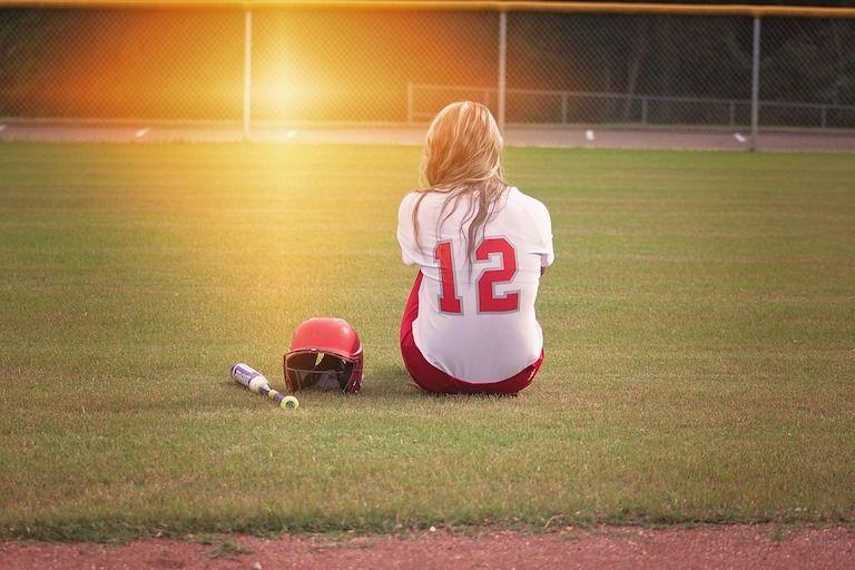 Szőke lány baseball mezben háttal ül a gyepen