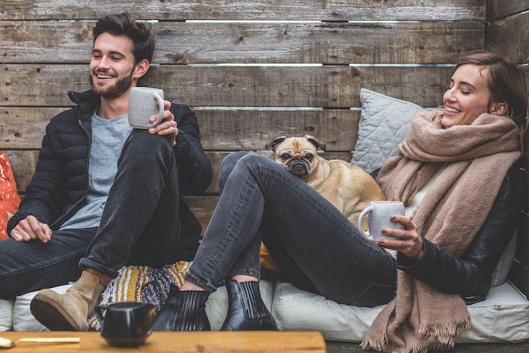 Pár hátradőlve a kanapén mosolyogva isznak teát egy mopsz társaságában