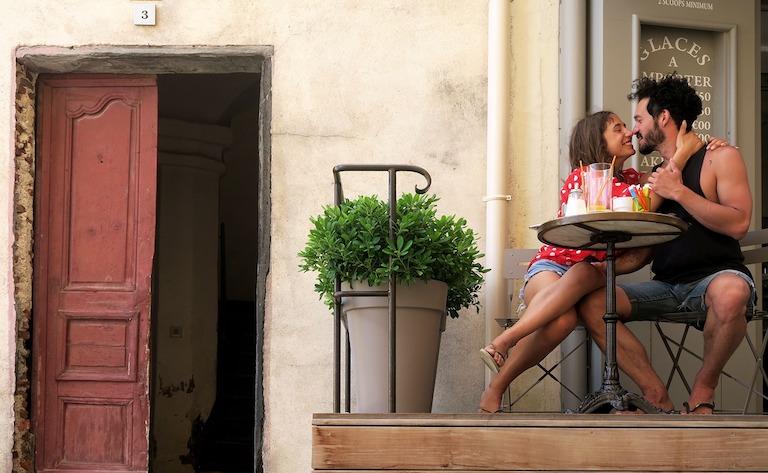 Csókra készülő szerelmespár kávézó teraszán