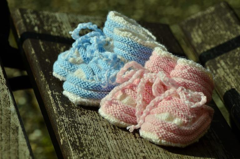 Két darab horgolt babacipő, az egyik kék, a másik rózsaszín
