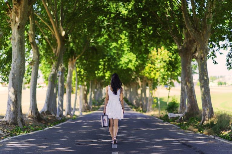 Nő fehér ruhában bőrönddel a kezében elfelé sétál fákkal szegélyezett úton